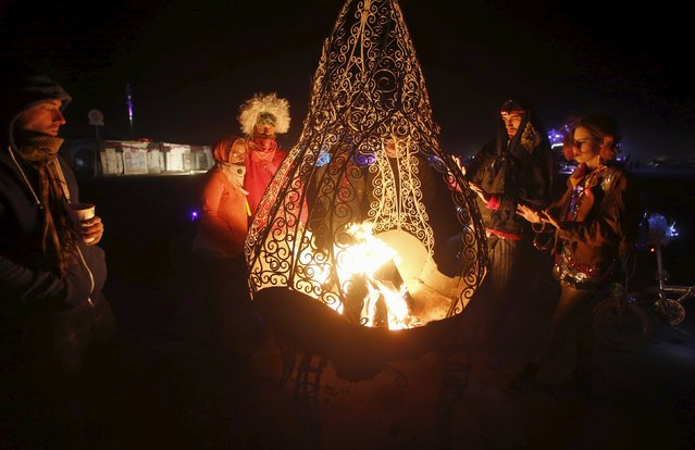 """Participants stay warm by a fire during the Burning Man 2015 """"Carnival of Mirrors"""" arts and music festival in the Black Rock Desert of Nevada, September 5, 2015. (Photo by Jim Urquhart/Reuters)"""