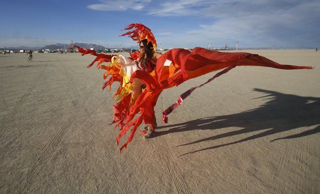 """Julia Kwinter dances on the Playa during the Burning Man 2015 """"Carnival of Mirrors"""" arts and music festival in the Black Rock Desert of Nevada, September 6, 2015. Sunday marks the last day of the sold-out festival that gathered approximately 70,000 people from all over the world. (Photo by Jim Urquhart/Reuters)"""