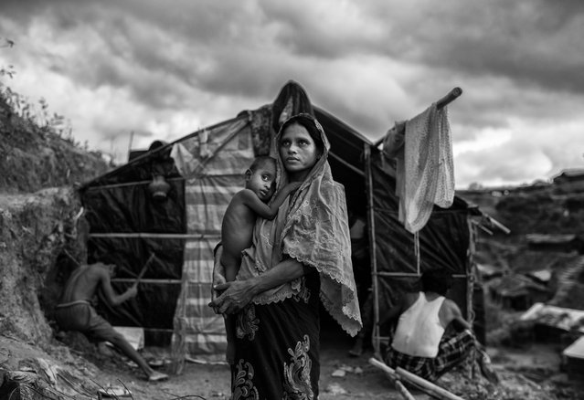 A Rohingya refugee woman holds her child as she stands outside her shelter at the sprawling Balukali refugee camp on September 27, 2017 in Cox's Bazar, Bangladesh. (Photo by Kevin Frayer/Getty Images)