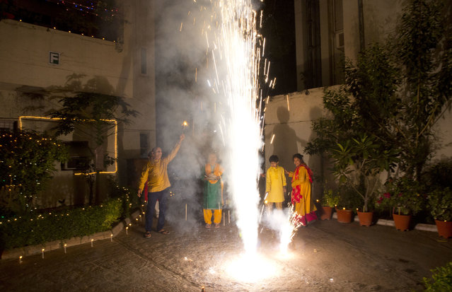 Indians play with firecrackers during Diwali festival in New Delhi, India, Thursday, October 19, 2017. Worried especially by the impact on the health of children, the Supreme Court this year banned the sale of firecrackers, that is usually in huge demand across the country as the evening sky is lit up by the festivities, in the Indian capital and neighboring areas to prevent a toxic haze after the Diwali nights that has residents hiding indoors. (Photo by Manish Swarup/AP Photo)