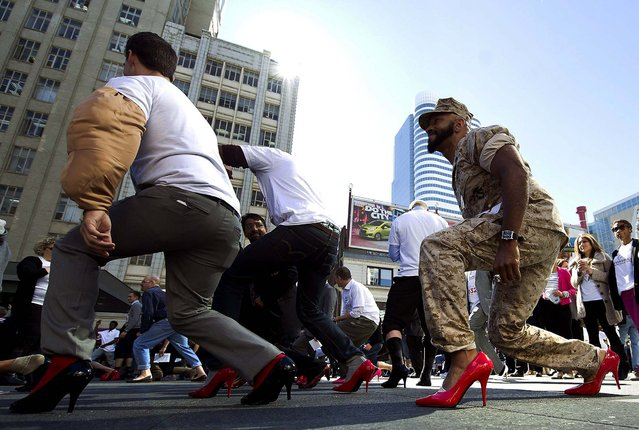 Former U.S. Marine Paul Lewis, right, and other men wearing women's high heels take part in the Walk a Mile in Her Shoes charity event in downtown Toronto, on September 27, 2012. The event is held to raise awareness and funds for the White Ribbon Campaign to end violence against women.  (The Mariendom (Cathedral of Mary), left, and St. Severi's Church are reflected in a puddle during Oktoberfest in Erfurt, Germany. (Photo by Jens Meyer/Associated Press/The Canadian Press)