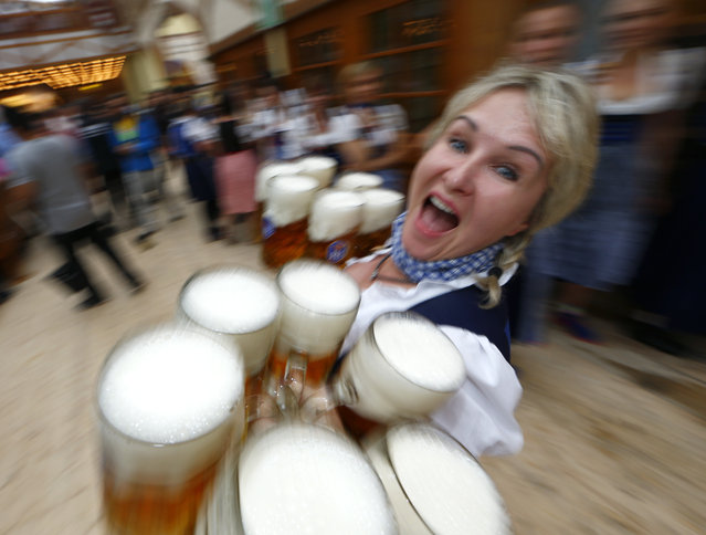 A waitress carries mugs of beer during the opening day of the 181st Oktoberfest in Munich September 20, 2014. (Photo by Michael Dalder/Reuters)