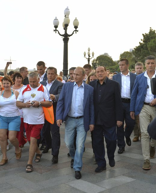 Russian President Vladimir Putin (3rd L, front) and former Italian prime minister Silvio Berlusconi (2nd R, front) walk along an embankment during their meeting in Yalta, Crimea, September 11, 2015. Berlusconi became the most prominent Western politician to visit Russian-annexed Crimea when he strolled beside the Black Sea on Friday with Putin. (Photo by Alexei Druzhinin/Reuters/RIA Novosti/Kremlin)