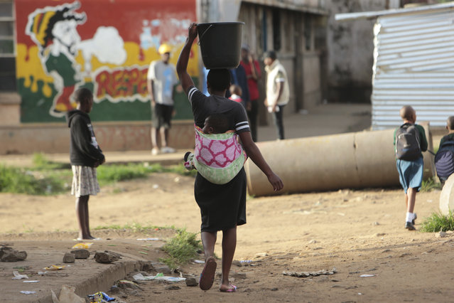 In this Monday, April 6, 2020 photo, a woman carries a her baby and a bucket of water in Harare. Lockdowns imposed to curb the coronavirus' spread have put millions of women in Africa, Asia and elsewhere out of reach of birth control and other sexual and reproductive health needs. Confined to their homes with husbands and others, they face unwanted pregnancies and little idea of when they can reach the outside world again. (Photo by Tsvangirayi Mukwazhi/AP Photo)