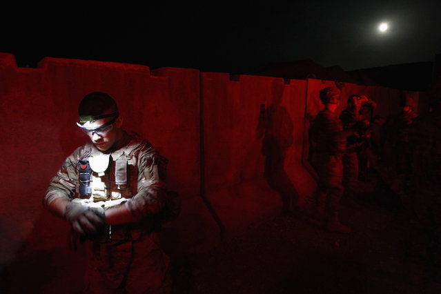 A U.S. Army soldier from Alpha troop, 4-73 Cavalry Regiment, 4th Brigade, 82nd Airborne Division checks his gear before a mission in the Maiwand district of Kandahar province, southern Afghanistan April 9, 2012. Picture taken April 9, 2012. (Photo by Baz Ratner/Reuters)