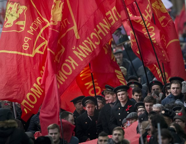Communist party supporters wearing a sailor's caps carry red flags during a demonstration marking the 100th anniversary of the 1917 Bolshevik revolution in Moscow, Russia, Tuesday, November 7, 2017. (Photo by Alexander Zemlianichenko/AP Photo)