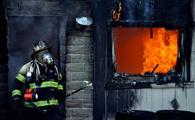 A firefighter works to extinguish a fire that destroyed an apartment building in Harwood near Hazleton, Pennsylvania,  October 16, 2012. Four people's homes were devastated in the blaze which is under investigation. (Photo by Ellen F. O'Connell/Hazleton Standard-Speaker)