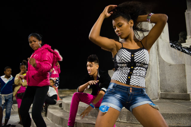 Late at night on Saturday, January 24, 2015, three young Cubans, from left to right, Daikelis Castellanos Silot, 15, Randol Rodriguez, 18, and Yasila Cateyano Suarez, 14, dance on the monument to the 266 U.S. sailors that died aboard the USS Maine which exploded in February 1898. The monument is fraught with symbolism of the complex relationship between the United States and Cuba. (Photo by Sarah L. Voisin/The Washington Post)