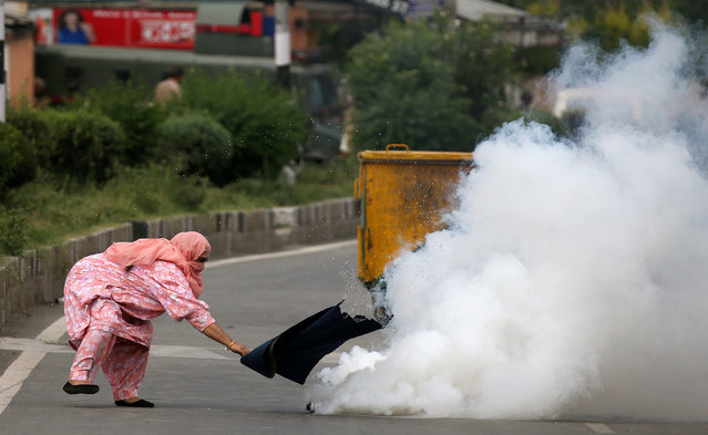 A woman attempts to cover a tear gas canister fired by police at a crowd in Srinagar protesting against the recent killings in Kashmir, August 17, 2016. (Photo by Cathal McNaughton/Reuters)