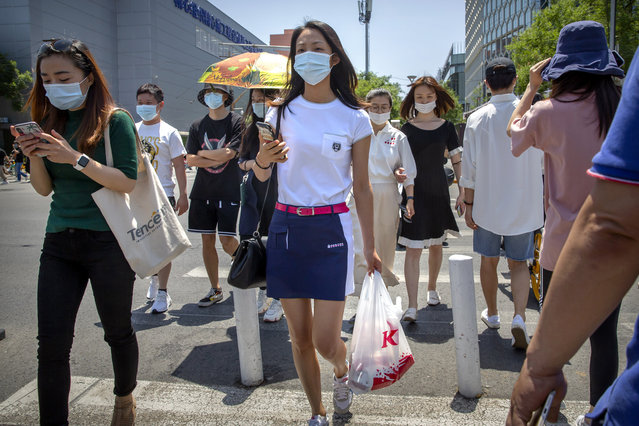 People wear face masks to protect against the coronavirus as they walk across an intersection in Beijing, Friday, June 5, 2020. China on Friday reported five new confirmed coronavirus cases, all of them brought by Chinese citizens from outside the country. (Photo by Mark Schiefelbein/AP Photo)