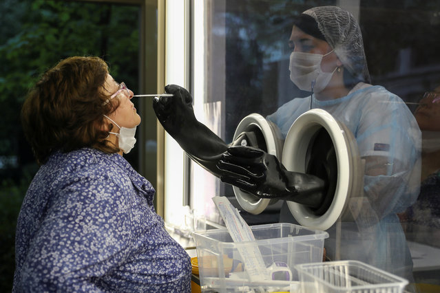 A staff member of AltraVita fertility clinic takes a swab from an outdoor booth as a woman undergoes a test for the coronavirus disease (COVID-19) in Moscow, Russia on June 10, 2020. The clinic added coronavirus testing to its list of services and installed a booth outdoors so clients can safely get tested for the disease. (Photo by Evgenia Novozhenina/Reuters)