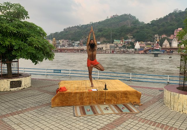 India's yoga guru Baba Ramdev performs yoga on the banks of the river Ganges ahead of International Yoga day, in the northern town of Haridwar, India, June 19, 2020. (Photo by Sunil Kataria/Reuters)