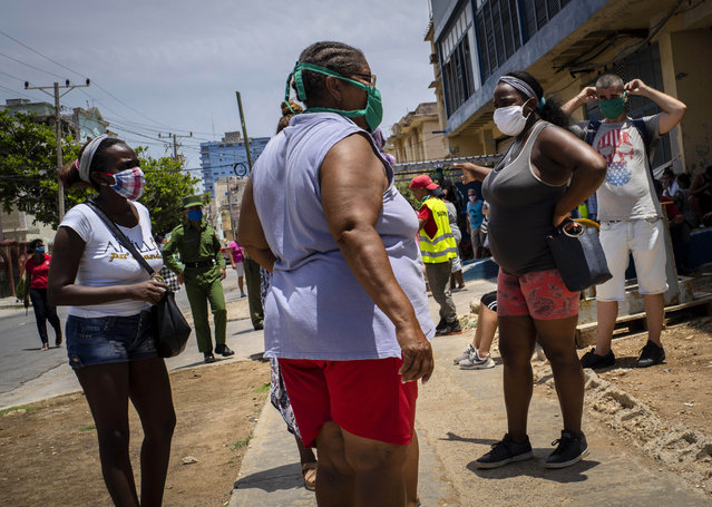 People wearing face masks amid the spread of the new coronavirus wait to enter a government-run food store in Havana, Cuba, Tuesday, May 19, 2020. State media has started a campaign of zero tolerance for anyone attempting to cash in on the fallout from the spread of the new coronavirus, like hoarding and speculative pricing, which has imposed even more distress on Cubans who were already used to shortages and long lines in their efforts to find basic necessities. (Photo by Ramon Espinosa/AP Photo)