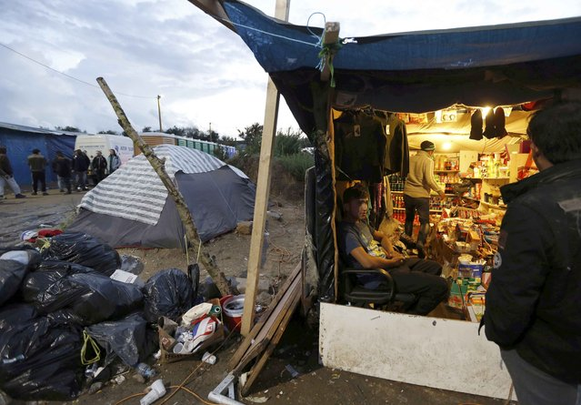 "Migrants stand at a makeshift shop near tents and shelters at the camp called ""The New Jungle"" in Calais, France, September 18, 2015. Around 3,500 migrants and refugees are camped in Calais, fleeing war and poverty in the Middle East, Africa and Asia and now living in the jungle. Most of them are hoping to make the crossing to England. (Photo by Regis Duvignau/Reuters)"