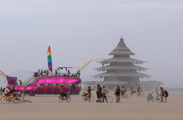 An art car and the Temple Project are visible on the Playa as approximately 70,000 people from all over the world gather for the 30th annual Burning Man arts and music festival in the Black Rock Desert of Nevada, U.S. August 29, 2016. (Photo by Jim Urquhart/Reuters)