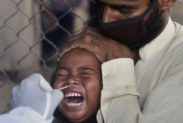 A girl reacts while getting a nasal swab sample at a testing and screening facility for the new coronavirus in a hospital in Karachi, Pakistan, Friday, July 17, 2020. (Photo by Fareed Khan/AP Photo)