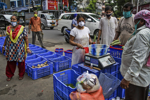People wearing masks as a precaution against the coronavirus buy vegetables in Kolkata, India, Tuesday, July 21, 2020. With a surge in coronavirus cases in the past few weeks, state governments in India have been ordering focused lockdowns in high-risk areas to slow down the spread of infections. (Photo by Bikas Das/AP Photo)