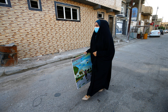 An Iraqi girl wearing a protective face mask carries an oil painting as she walks to her shop, after the government partially lifted the curfew imposed to fight the spread of the coronavirus disease (COVID-19), in the holy city of Najaf, Iraq on July 6, 2020. (Photo by Alaa Al-Marjani/Reuters)
