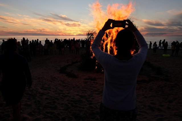 A woman takes a picture of a bonfire during the Livonian fire ceremony at the seaside in Mazirbe, Latvia on August 1, 2020. (Photo by Ints Kalnins/Reuters)