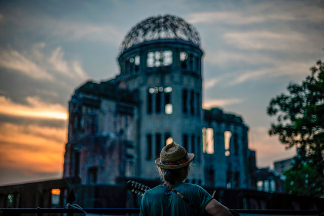 A man plays his guitar in front of in front of ruins of the Hiroshima Prefectural Industrial Promotion Hall, now commonly known as the atomic bomb dome, during sunset in Hiroshima on August 5, 2020. Japan on August 6, 2020 will mark 75 years since the world's first atomic bomb attack, with the COVID-19 coronavirus pandemic forcing a scaling back of annual ceremonies to commemorate the victims. (Photo by Philip Fong/AFP Photo)