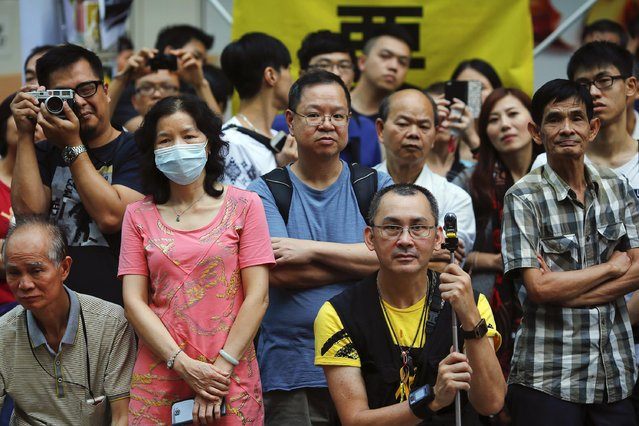 People listen to a pro-democracy protester delivering a speech from a makeshift stage at the part of Mongkok shopping district protesters are occupying in Hong Kong November 2, 2014. (Photo by Damir Sagolj/Reuters)