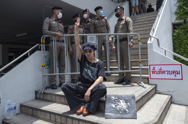 A pro-democracy supporter raises a three-finger salute, a symbol of resistance, in front of police officers at the Samranrat police station in Bangkok, Thailand, Thursday, August 20, 2020. Thai police arrested a rapper and four pro-democracy activists in a crackdown on growing protests that have emerged as the most serious threat to the government led by a former army general they accuse of incompetence and corruption. (Photo by Sakchai Lalit/AP Photo)