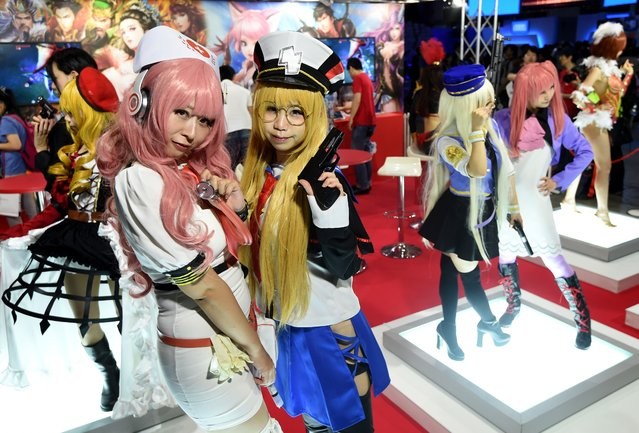 Models clad in costumes of video game charactors pose at a game booth during the Tokyo Game Show 2016 in Chiba, suburb of Tokyo, on September 15, 2016. Sony took centre stage at the annual four-day event, with its virtual reality headset ready to hit store shelves for the Christmas shopping season. (Photo by Toru Yamanaka/AFP Photo)