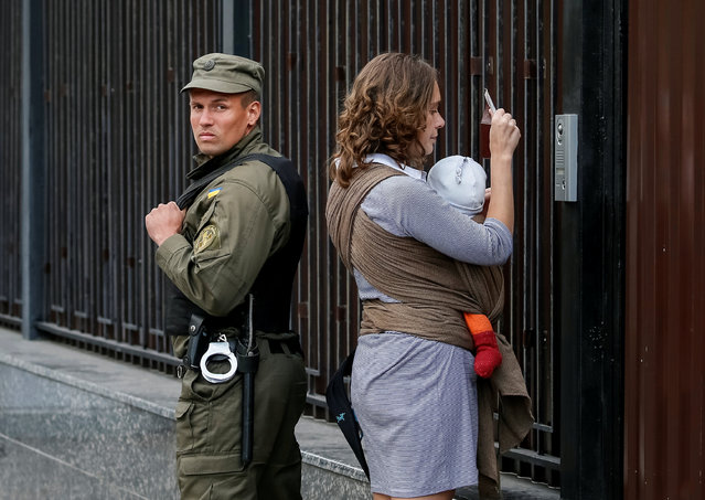 A woman shows her passport to enter the Russian embassy and take part in the Russian parliamentary election as a member of the National Guard stands guard in Kiev, Ukraine, September 18, 2016. (Photo by Gleb Garanich/Reuters)