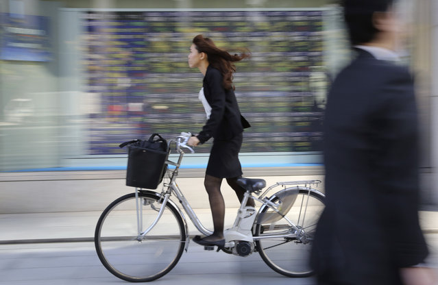A woman cycles past an electronic stock board of a securities firm in Tokyo, Monday, November 10, 2014. Asian stock markets were mostly higher Monday after the release of strong U.S. jobs figures and weekend data showing China's exports remained on an upward trend. (Photo by Koji Sasahara/AP Photo)