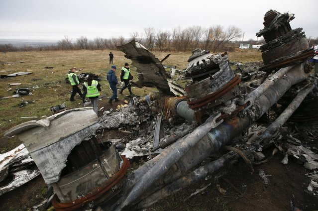 Dutch investigators and an Emergencies Ministry member work at the site where the downed Malaysia Airlines flight MH17 crashed, near the village of Hrabove (Grabovo) in Donetsk region, eastern Ukraine November 16, 2014. (Photo by Maxim Zmeyev/Reuters)