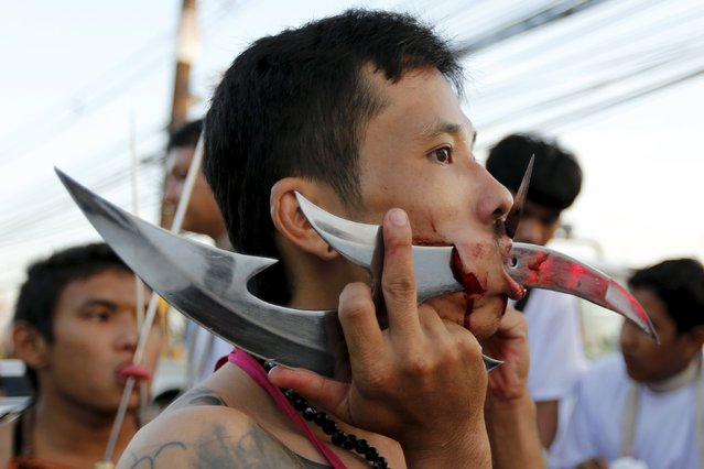 A devotee of the Chinese Ban Tha Rue shrine have knives pierced through his cheeks during a procession celebrating the annual vegetarian festival in Phuket, Thailand, October 17, 2015. (Photo by Jorge Silva/Reuters)