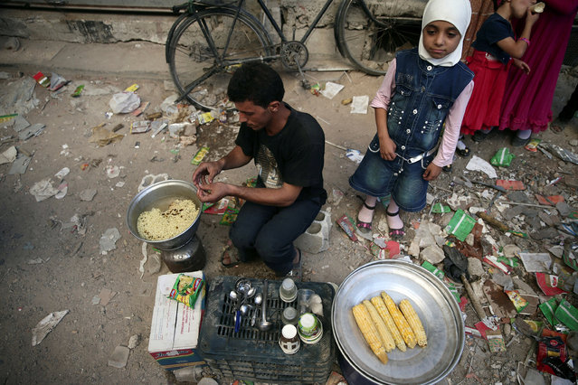 A vendor sells corn on the cob and noodles on the last day of Eid al-Adha celebrations in the rebel held besieged town of Hamouriyeh, eastern Ghouta, near Damascus, Syria September 15, 2016. (Photo by Bassam Khabieh/Reuters)