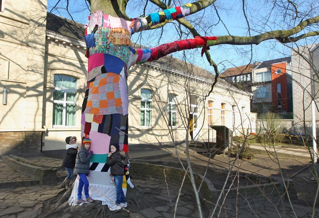 Kids hug a tree covered by knitted materials, at their school in Ghent, Belgium, Monday, March 4, 2013. The school wants to show their affection for the sole tree in the schoolyard by giving it a coat for the winter. (Photo by Yves Logghe/AP Photo)