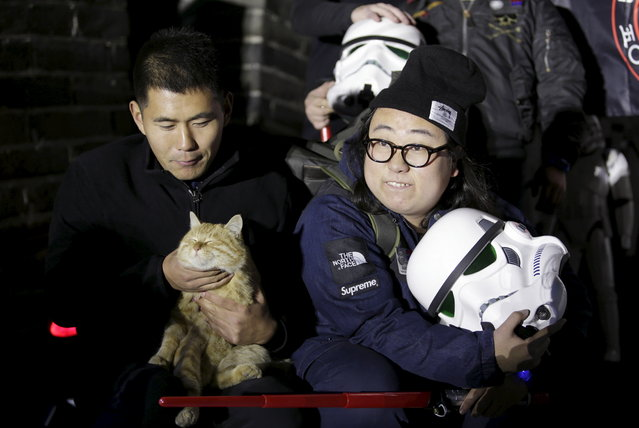 """A fan holding a helmet of the Stormtrooper character from """"Star Wars"""" poses for a group photo next to a cat at the Juyongguan section of the Great Wall of China during a promotional event for """"Star Wars: The Force Awakens"""" film, on the outskirts of Beijing, China, October 20, 2015. (Photo by Jason Lee/Reuters)"""