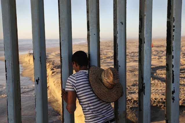 A man looks through the U.S.-Mexico border fence into the United States on September 25, 2016 in Tijuana, Mexico. Friendship Park on the border is one of the few places on the 2,000-mile border where separated families are allowed to meet. (Photo by John Moore/Getty Images)