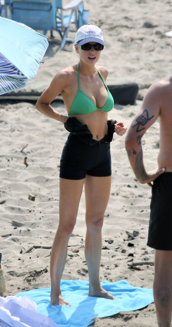 American actress and model Charlotte McKinney joins her boyfriend Nathan Kostechko and some friends for a day at the beach in Los Angeles on October 5, 2020. The 27 year old actress and model carried a mini surfboard and wore a green bikini under a black wetsuit. (Photo by TheImageDirect.com)