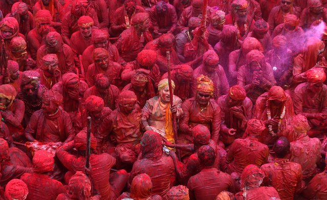 Indian Hindu devotees smeared with colors sing at the Nandagram temple, famous for Lord Krishna and his brother Balram, during Lathmar holy festival, in Nandgaon, India, Friday, March 22, 2013. During Lathmar Holi the women of Nandgaon, the hometown of Krishna, beat the men from Barsana, the legendary hometown of Radha, consort of Hindu God Krishna, with wooden sticks in response to their teasing as they depart the town. (Photo by Manish Swarup/AP Photo)