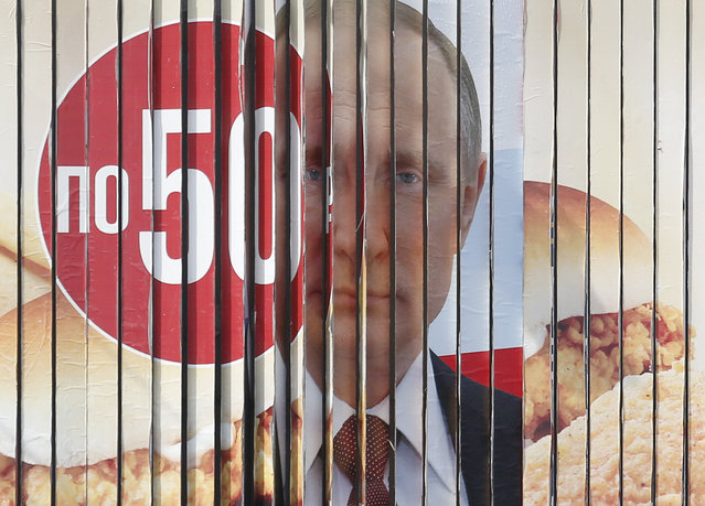 A multi-sided transformable board, which advertises the campaign of Russian President Vladimir Putin ahead of the upcoming presidential election, is on display in a street in Stavropol, Russia March 5, 2018. (Photo by Eduard Korniyenko/Reuters)