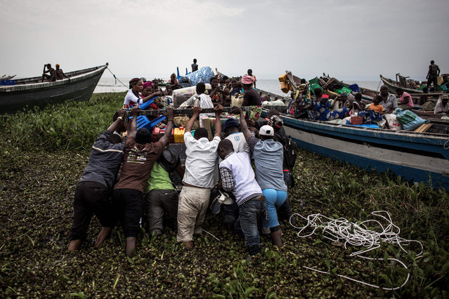 Internally displaced Congolese push a boat out, as its sets off to escape over Lake Albert to Uganda on March 05, 2018 in Tchomia. Displaced Congolese, fleeing inter- communal violence in the Ituri region of the Democratic Republic of the Congo, make their way to the Tchomia on the DRC side of Lake Albert in search of safety and boats to make the crossing to the safety of the refugee camps in Uganda. (Photo by John Wessels/AFP Photo)