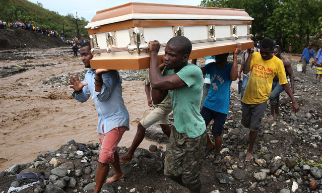 A group of people carry a coffin and try to cross the river La Digue, after the colapse of the only bridge that connects to the south after the passing of hurricane Matthew in the country, in Petit Goave, Haiti, 05 October 2016. (Photo by Orlando Barria/EPA)