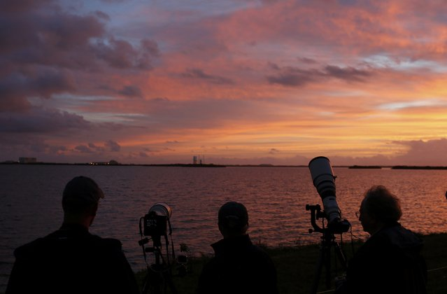 News photographers and journalists watch as the sun rises on the Delta IV Heavy rocket carrying the Orion spacecraft waiting for liftoff  on the launch pad from the Cape Canveral Air Force Station in Cape Canaveral, Florida December 4, 2014. (Photo by Scott Audette/Reuters)