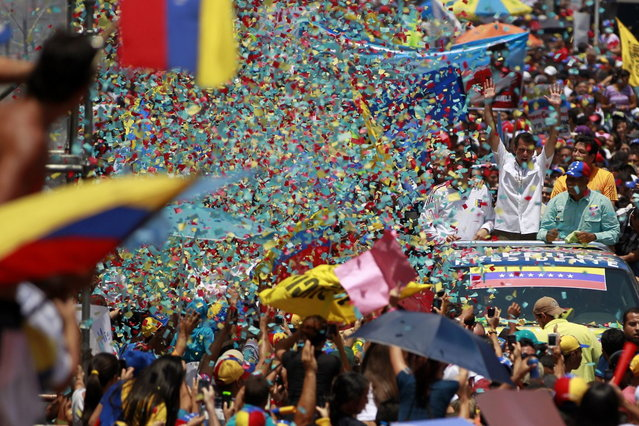 Venezuela's opposition leader and presidential candidate Henrique Capriles (R) greets supporters during a campaign rally in the state of Guarico April 8, 2013. Venezuela will hold presidential elections on April 14. (Photo by Carlos Garcia Rawlins/Reuters)