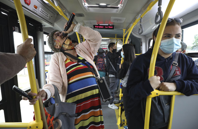 "Marlene Alfonso, a 69-year-old Venezuelan grandmother who goes by the name ""Toothless Cindy"", sings about Venezuelan migrants' lives in hopes of tips from commuters on the Transmilenio, the crowded and crime-ridden public bus system in Bogota, Colombia, Tuesday, November 3, 2020. Alfonso suffers from glaucoma and cannot see out of her left eye, thus can't see the buttons on her speaker's remote control properly, so she asks commuters for help to play the right tracks. (Photo by Fernando Vergara/AP Photo)"