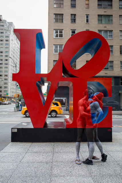 A coupe blend into each other and the famous LOVE statue whilst sharing an intimate moment in New York City, US. (Photo by Trina Merry/Caters News)