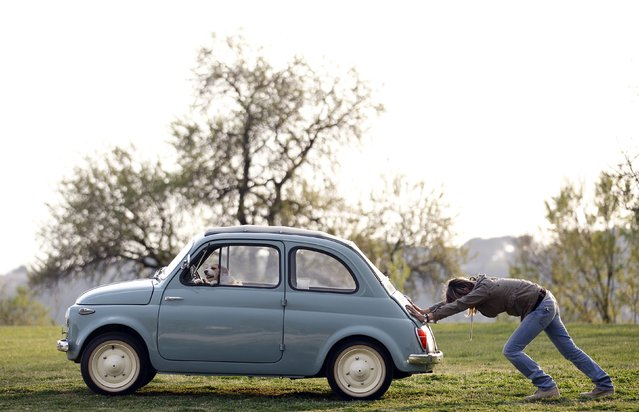 A woman pushes her Fiat 500 car as her dog sits inside, in a neighbourhood of Rome in this March 23, 2012 file photo. (Photo by Alessandro Bianchi/Reuters)