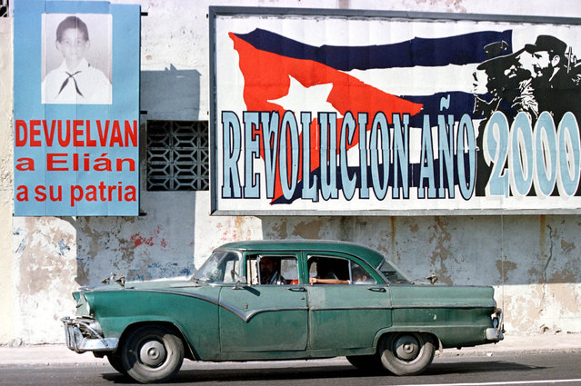 A 1955 Ford drives past two billboards referring to Elian Gonzalez, in Old Havana City, in a file photo. (Photo by Rafael Perez/Reuters)