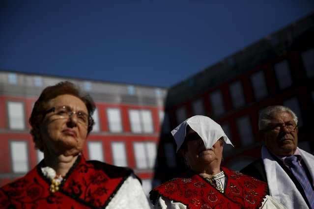 A woman in traditional costume shades her face from the sun during an open-air mass to celebrate Madrid's patron saint La Almudena Virgin in Madrid, Spain, November 9, 2015. (Photo by Susana Vera/Reuters)