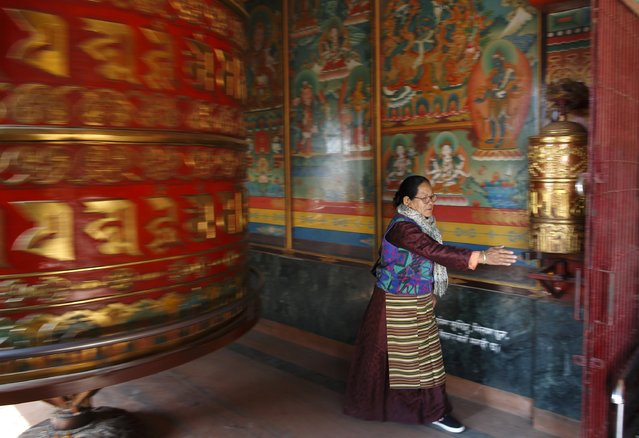A Buddhist devotee spins prayer wheels while offering daily prayers at the premises of Boudhanath Stupa in Kathmandu December 23, 2014. Listed as a world heritage site by UNESCO, the Boudhanath Stupa is considered one of the holiest places for Buddhists. (Photo by Navesh Chitrakar/Reuters)