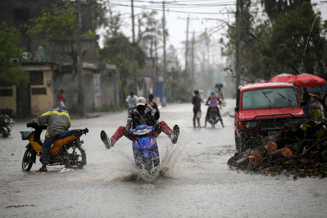 A man riding a motorbike drives on a flooded street during rain after Hurricane Matthew in Les Cayes, Haiti, October 17, 2016. (Photo by Andres Martinez Casares/Reuters)