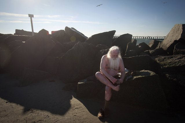 Dick Shea gets dressed after taking part in the Polar Bear Plunge on Coney Island in the Brooklyn borough of New York January 1, 2015. (Photo by Carlo Allegri/Reuters)